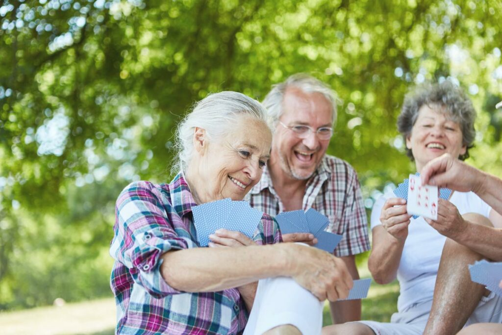 The Gardens of Castle Hills | Seniors playing cards outdoors